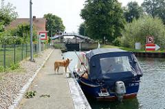Ein Sportboot wartet vor der Schleuse in Plau am See auf die Schleusung - ein Hund steht an Land.