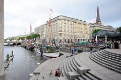 Kleine Alster am Hamburger Rathausmarkt - historische Ewer liegen am Kai - Kirchturm der St. Petrikirche.