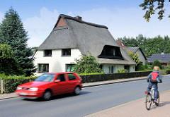 Reetgedecktes Wohnhaus mit weisser Putzfassade - fahrendes Auto, Fahrradfahrer; Kisdorfer Strasse in Henstedt / Henstedt-Ulzburg.