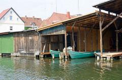 Bootshäuser von Fischerbooten am Ufer der Elde Müritz Wasserstrasse in Plau am See.