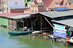 Bootshäuser in Plau am See - ein Fischer legt mit seinem Boot im Bootshaus an.