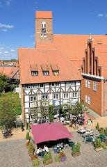 Blick von oben auf den Schuhmarkt in Parchim - Eiscafe, Gäste unter Sonnenschirmen - St. Georgenkirchen