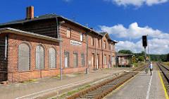 Stillgelegtes Bahnhofsgebäude von Neustadt Glewe; Ziegelgebäude, vernagelte Fenster - Fahrgast auf dem Bahnsteing; blauer Himmel, weisse Wolken.