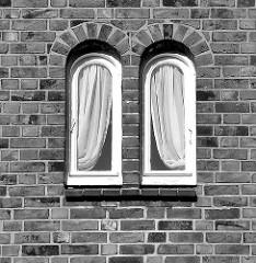 Schmale Fenster mit Gardinen / symmetrisch - Backsteinfassade in Hamburg Alsterdorf; schwarz - weiss Aufnahme.
