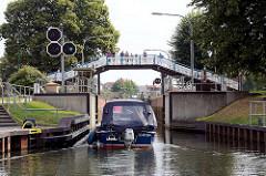 Ein Motorboot fährt in die Schleuse in Plau am See -  Zuschauer / Touristen stehen auf der Fussgänerbrücke / Holzbrücke über der Schleuse.
