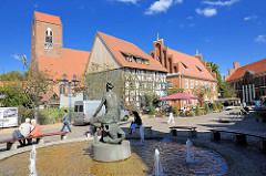 Brunnen, Weib auf Stierkopf - Schuhmarkt in Parchim - historische Architektur; St. Georgenkirche, Wohnhäuser / Geschäftshäuser.