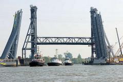 Drei Schlepper passieren die hochgefahrene Rethehubbrücke in Hamburg Wilhelmsburg und fahren vom Reiherstieg in die Rethe ein. Im Vordergrund Teile der Brückenkonstruktion für die neue Klappbrücke.
