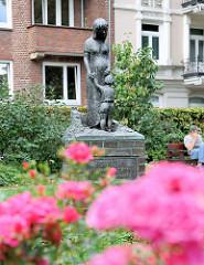 Bronzestatue Mutter mit Kind; Inschrift SAG NEIN! Wolfgang Borchert - Rosenrabatte an der Eppendorfer Landstrasse in Hamburg Eppendorf.