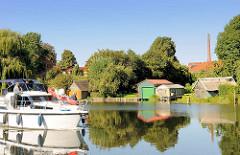Bootsschuppen am Ufer der Müritz-Elde-Wasserstrasse in Lübz; ein Motorboot in Fahrt.