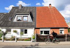 Doppelhäuser unterschiedliche Fassadengestaltung und eingedeckte Dächer; Fahrradfahrerin.