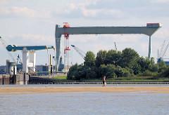 Blick über die Elbe zur Estemündung - Klappbrücke über die Strasse - 300 t Werftkran der Sietas Werft. Ein Spaziergänger auf dem Watt, das bei Niedrigwasser im Mühlenberger Loch entsteht.