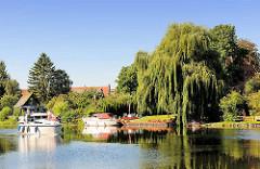 Müritz-Elde-Wasserstrasse in der Kleinstadt Lübz - die Zweige einer hohen Weide hängen ins Wasser - Motorboote.