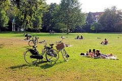 Sommerabend im Haynspark in Hamburg Eppendorf - abgestellte Fahrräder, ParkbesucherInnen auf der Wiese in der Sonne.