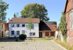 Einstöckiges Wohnhaus mit verputzter weisser Fassade - verfallener Schuppen als Anbau; Bilder aus Lübz - Mecklenburg Vorpommern.