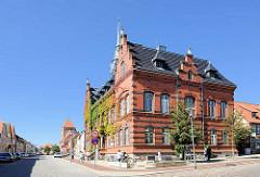 Rathaus von Plau am See - Backsteinbau, 1888 im Stil der Neorenaissance errichtet. Im Hintergrund die St. Marienkirche.