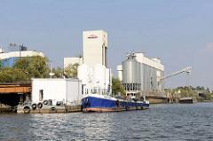 Silos auf einem Arbeitsboot und am Ufer der Rethe in Hamburg Wilhelmsburg; Entsorgungsschiff DON MULI.