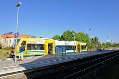 Regionalzug der Südbahn am Bahnsteig in Lübz - ein Reisender steigt aus.
