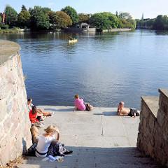 Sommer in Hamburg - Eppendorfer Haynspark an der Alster - Besucherinnen sitzen am Wasser in der Sonne - ein Kanu fährt auf der Alster.