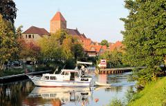 Sportboot auf dem Müritz-Elde-Wasserweg in Plau am See - Kirchturm der St. Marienkirche.