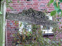 Altes Strassenschild - Holzschild von Hand geschnitzt; An der Blütenmauer in der Gartenstadt von Hamburg Alsterdorf.