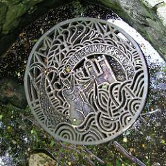 Eisenplatte mit Seejungfrau / Nixe und Hamburg Wappen an der Alsterquelle in Rhen / Henstedt Ulzburg; Inschrift Quellgrund der Alster.