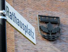 Schild Rathausplatz - Gemeindewappen von Henstedt-Ulzburg; dreiblättriger Echenzweig, Mauerkrone + Wellenfäden.