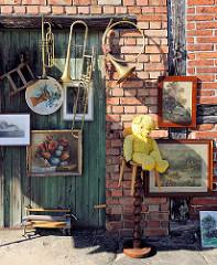 Trödelladen in der Schweriner Strasse von Neustadt Glewe; Bilderrahmen und Musikinstrumente an der Ziegelwand.