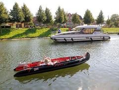 Schiffsverkehr auf der Müritz-Elde-Wasserstrasse in Plau am See; Schlauchboot und Motorboot.