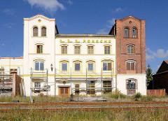 Teilweise renoviertes, gestrichenes Lagergebäude / Fabrikgebäude an den Bahngleisen von Neustadt Glewe - die Ziegelfassade / Backsteinfassade ist teilweise weiss gestrichen.