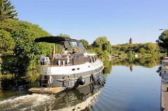 Motorboot in Fahrt auf der Müritz - Elde - Wasserstrasse in Lübz; im Hintergrund der alte Wasserturm der Stadt.