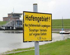 Schild Hafengebiet - im Hintergrund die Schleuse am Friedrichskooger Hafen.