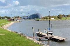 Hafen von Friedrichskoog / Dithmarschen. Ein Segelboot liegt am Steg. Im Hintergrund die Architektur vom Wal-Gebäude, das einen Indoorspielplatz beinhaltet.
