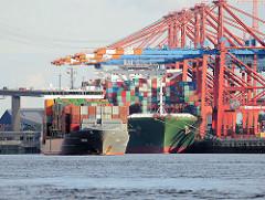 Ein Containerfeeder hat im Waltershofer Hafen abgelegt und verlässt den Hamburger Hafen - Containerschiff unter Containerkränen am Terminal Eurogate.