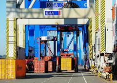 Vom Frachtschiff entladene Container werden von den Portalhubwagen weiter transportiert.