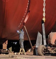 Ein Werftarbeiter schweisst an einem Schiffsrumpf - der Schiffsanker hängt an einer schweren Kette auf dem Boden des Docks einer Werft auf Hamburg STeinwerder.