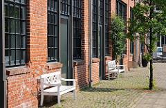 Architekturgeschichte Hamburgs - Industriearchitektur der Gründerzeit - Kopfsteinpflaster und Holzbänke beim Phönixhof in Hamburg Ottensen.