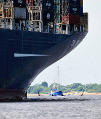 Bug eines Containerfrachters mit Containern beladen - Fischkutter beim Fang auf der Elbe vor Hamburg Finkenwerder.