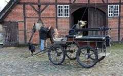Kutsche und Kutschpferd auf Kopfsteinpflaster im Volksdorfer Museumsdorf.