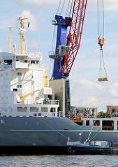 Die Fracht wird mit einem Kran an Bord des Schiffs gebracht, das am Sthamer Kai des Hamburger Oderhafens liegt. Ein Tankschiff hat längsseits festgemacht.