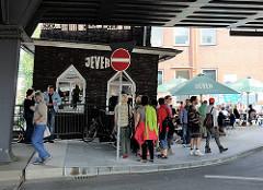 Oberhafenkantine am Oberhafenkanal bei der Oberhafenbrücke - Gaststätte in der Hafencity Hamburg. Gäste sitzen unter Sonnenschirmen an der STrasse.