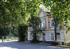 Gründerzeitwohnhaus am Ufer der Berner Au - Blätter der Strassenbäume im Sonnenlicht.