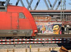 Eisenbahnstrecke an der Versmannstrasse; Graffiti an einer Hauswand - Lokomotive.