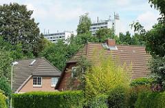 Einzelhäuser mit Satteldach, Seitenstrasse Hamburg Langenbek - Hochhäuser von Hamburg Sinstorf im Hintergrund.
