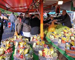 Marktstand mit Früchten auf dem Altonaer Fischmarkt - Basttaschen sind mit unterschiedlichen Früchten gefüllt und warten auf KäuferInnen.