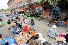 Openairauftritt von Musikgruppen im Knust im Gebäude der alten Rinderschlachthalle - die ZuhörerInnen sitzen im Freien an Tischen und hören der Musik zu.