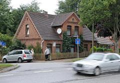 Historisches Backsteingebäude an der Hauptstrasse in Hamburg Langenbek - Fotos aus den Hamburger Stadtteilen - Strassenverkehr; schnell fahrendes Auto.