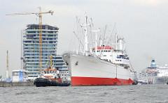Das Museumsschiff Cap San Diego fährt mit Schlepperhilfe - im Hintergrund Baustelle der Hafencity am Strandkai. (2009)