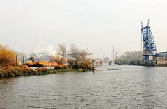 Blick von der ALTEN SÜDERELBE zum Kran und Kai des Dradenauhafens.