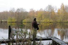 Angler auf einem Steg im Volksdorfer Rueckhaletbecken an den Teichwiesen.