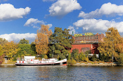 Altes Hausboot am Hochwasserbecken - Bäume mit Herbstblättern, weisse Wolken; im Hintergrund grosses Grafitti an der Fassade eines alten Industriegebäudes.